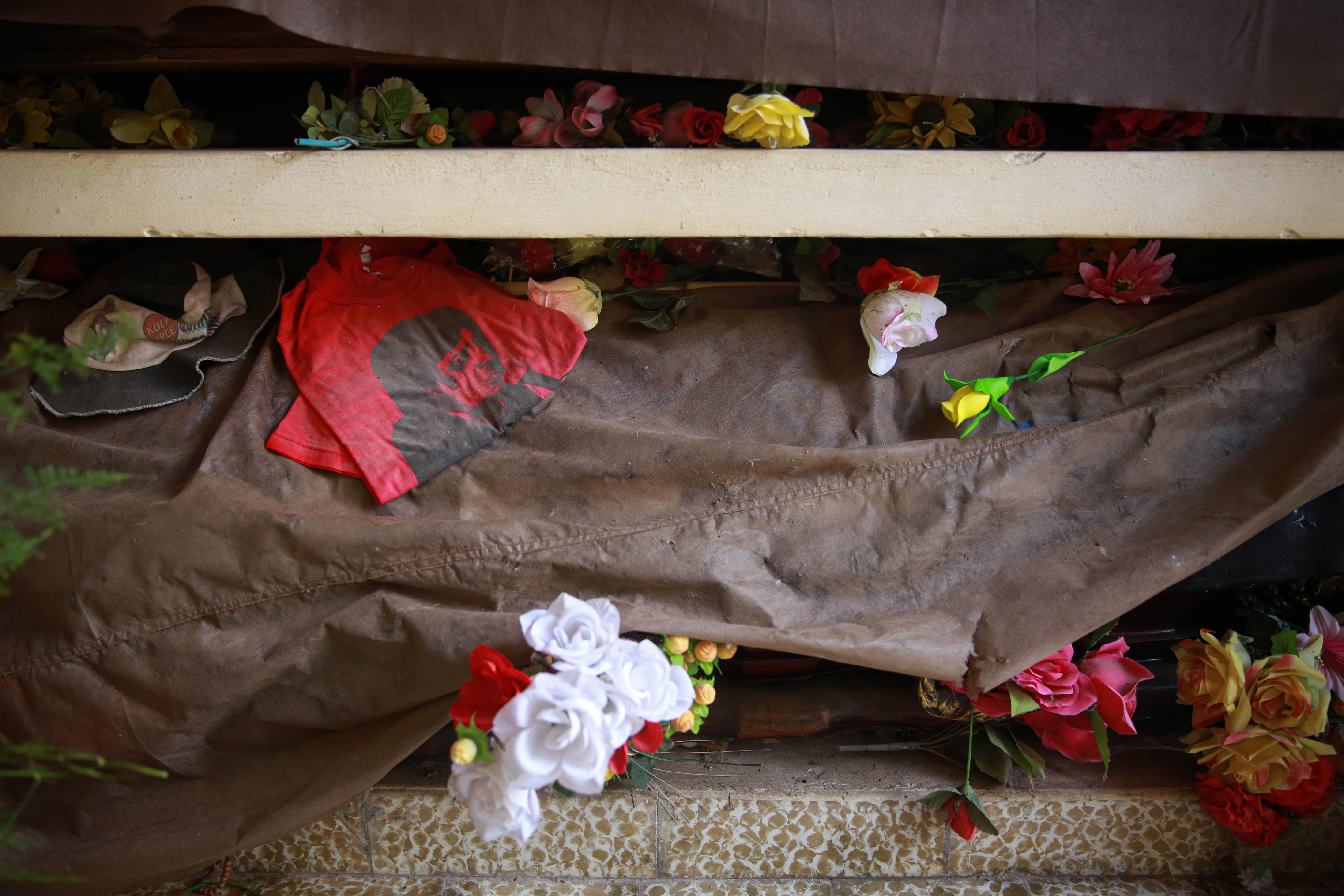 El mausoleo donde descansan los restos de Koli, acompañado de remeras, gorros, rosarios y otros objetos que sus fans le dejan.